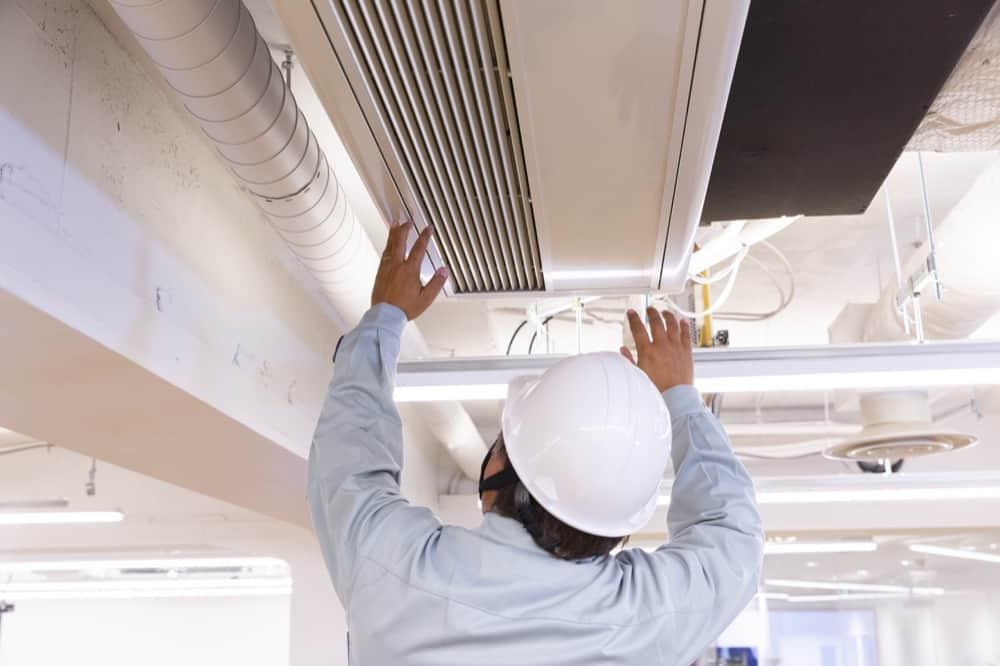 ouvrier fixant une clim dans un faux-plafond
